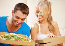 Romantic couple eating pizza at home. Picture of happy romantic couple eating pizza at home (focus on woman Stock Photos