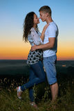 Romantic couple embrace at sunset, beautiful landscape and bright yellow sky, love tenderness concept, young adult people Stock Photography
