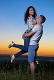 Romantic couple embrace at sunset, boyfriend raise up girlfriend, beautiful landscape and bright yellow sky, love tenderness conce. Pt, young adult people Royalty Free Stock Images