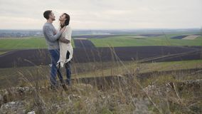 Romantic couple in embracess and kisses stand on the top of rock