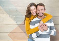 Romantic couple embracing each other against wooden background Stock Images