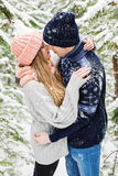 Romantic couple embracing in snowy forest among fir trees Stock Image