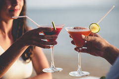 Romantic couple enjoy sunset in restaurant on the beach drinking cocktails Royalty Free Stock Images