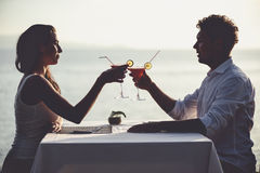 Romantic couple enjoy sunset in restaurant on the beach drinking cocktails Royalty Free Stock Photos