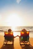 Romantic Couple Enjoying Beautiful Sunset holding hands. Happy Romantic Couple Enjoying Beautiful Sunset at the Beach royalty free stock image