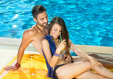 Romantic couple enjoying cocktails at the pool. Stock Photo