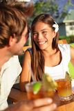 Romantic couple enjoying drinks at beach club. Talking smiling and laughing on Hawaii drinking alcoholic beverage Mai Tai cocktails. Lovers having fun together Stock Photo