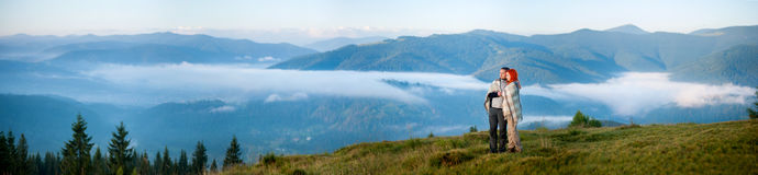 Romantic couple enjoying a morning haze over the mountains. Charming couple toourists covered with a plaid standing together on a hill, enjoying beautiful Stock Photo