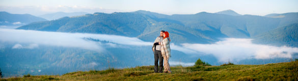 Romantic couple enjoying a morning haze over the mountains Royalty Free Stock Images