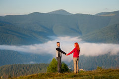Romantic couple enjoying a morning haze over the mountains Stock Images