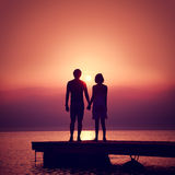 Romantic Couple Enjoying Sunset at Sea. Romantic Couple in Love Holding Hands and Enjoying Sunset at Sea.  Toned and Filtered Square Photo with Copy Space. Man Stock Images