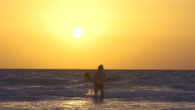 Romantic couple is falling in love on the beach at sunset, kiss each other. Happy Young man is circling the girl in his