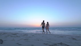 Romantic couple is falling in love on sea. Man with woman is holding hands and walking along the wet sandy beach. Two. Hipster in love, kiss each other. Sexy stock video