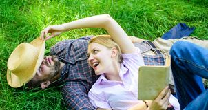 Romantic couple family enjoy leisure with poetry or literature grass background. Couple soulmates at romantic date. Man. And girl lay on grass relaxing. Couple stock photography