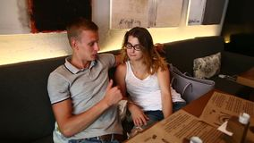 Romantic couple female male sitting together in cafe with phone stock video footage