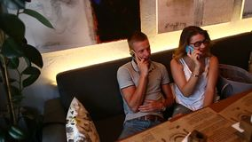 Romantic couple female male sitting together in cafe talk on pho. Young beautiful couple sitting in cafe lifestyle hug, talk, technology gadgets, coffee stock footage