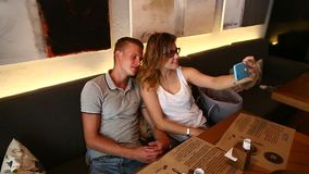 Romantic couple female male take make selfie sitting together in. Young beautiful couple sitting in cafe lifestyle hug, talk, technology gadgets, coffee stock footage