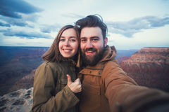 Romantic couple or friends show thumbs up and make selfie photo on travel hiking at Grand Canyon in Arizona Royalty Free Stock Photography
