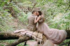 Romantic couple is gently hugs on the log. Autumn wedding Stock Photography