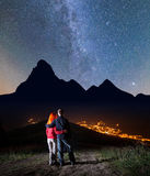 Romantic couple - girl and guy embracing each other, standing on a hill under the bright stars and Milky way Stock Image