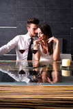 A romantic couple with a glass of wine in the dining room Stock Images