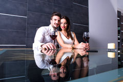 A romantic couple with a glass of wine in the dining room Stock Image