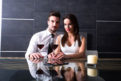 A romantic couple with a glass of wine in the dining room Stock Photography
