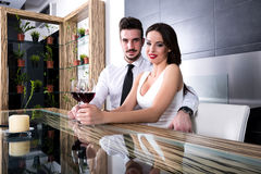 A romantic couple with a glass of wine in the dining room Royalty Free Stock Image