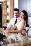 A romantic couple with a glass of wine in the dining room Royalty Free Stock Photography