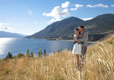 Romantic Couple in Grassy Field. Outdoor photo of young couple embracing in grassy field at scenic viewpoint stock images