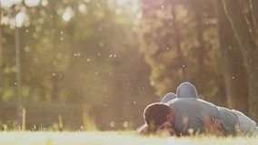 Romantic couple on a green glade in summer. They play with each other, lying on the grass. Happy together in the rays of. Sunlight stock video footage