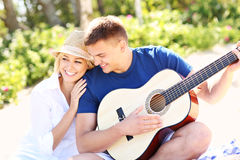 Romantic couple and guitar on the beach Stock Images