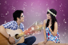 Romantic couple with guitar singing together Stock Photos