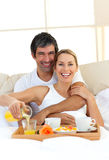 Romantic couple having breakfast lying in the bed Stock Image
