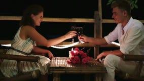 Romantic couple having dinner, clinking glasses stock video footage