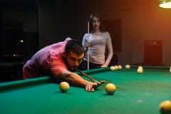 Romantic couple having fun playing billiard game Stock Images