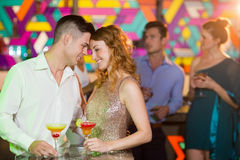 Romantic couple having glass of cocktail. Happy romantic couple having glass of cocktail in bar stock photography