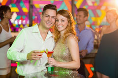 Romantic couple having glass of cocktail. Portrait of romantic couple having glass of cocktail in bar stock photo