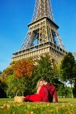 Romantic couple having picnic on the grass near the Eiffel tower royalty free stock photo