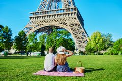 Couple having picnic near the Eiffel tower in Paris stock image