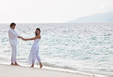 Romantic couple having a walking on the sea shore Stock Photography