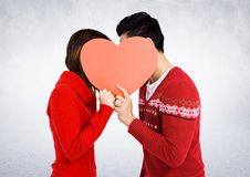 Romantic couple hiding their face behind heart Stock Photography