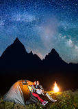 Romantic couple hikers looking to the shines starry sky and Milky way in the camping at night near campfire Royalty Free Stock Image