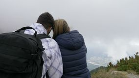 Romantic couple hiking standing together on mountain peak kissing and enjoying the breathtaking landscape - stock video footage