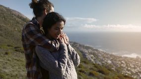 Romantic couple on hill top. Man holding the woman from behind and laughing while standing together on hill. Romantic couple standing on a hill embracing stock video