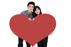 Romantic couple holding a big red heart Royalty Free Stock Photo