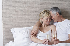 Romantic Couple Holding Champagne Flutes In Bed Stock Photography