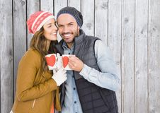 Romantic couple holding coffee mugs. Against wooden background Stock Photography