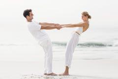 Romantic couple holding hands on the beach Stock Photos