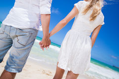 Romantic couple holding hands on the beach. Royalty Free Stock Photos